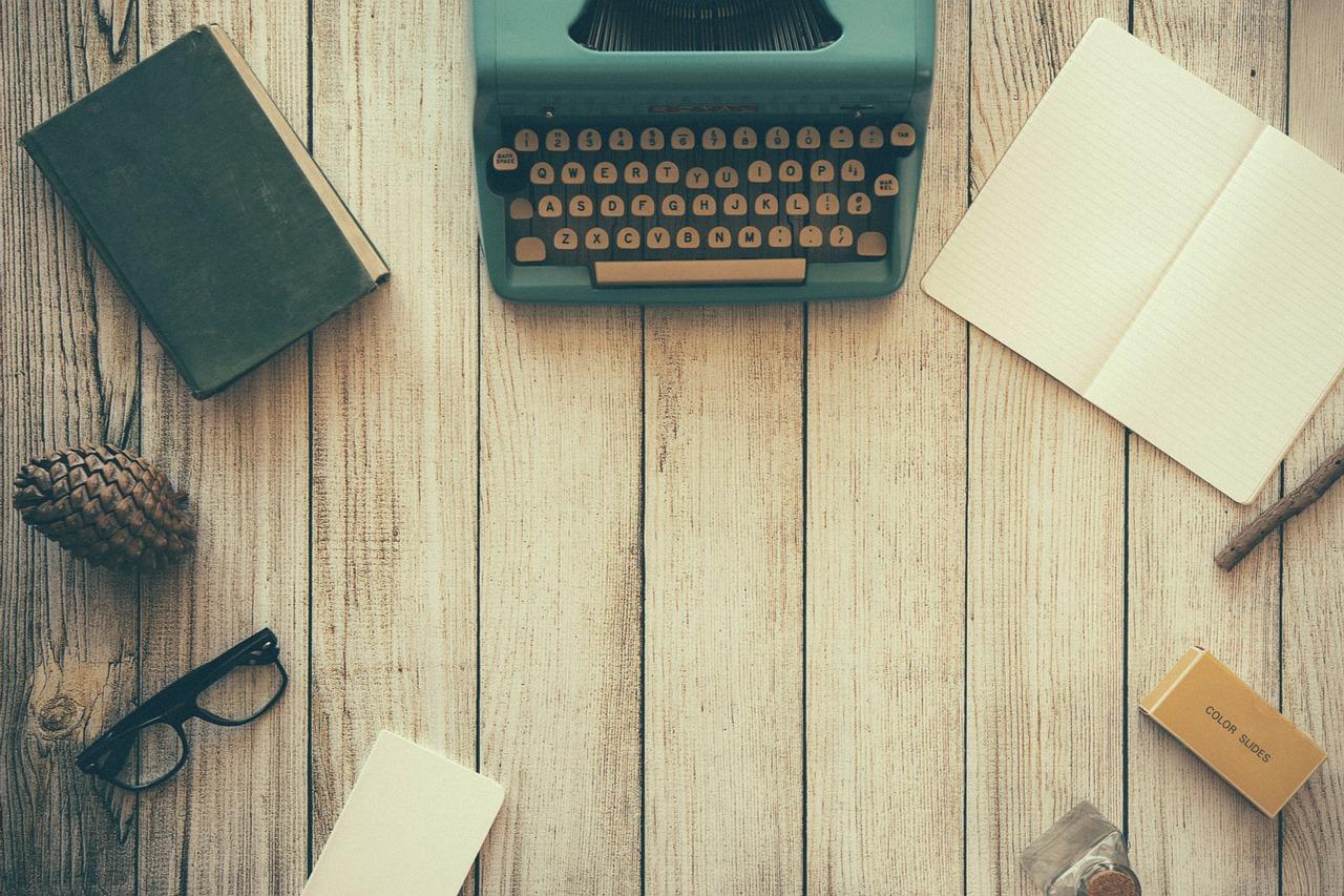 Skrivbord med pärmar, skrivmaskin och papper